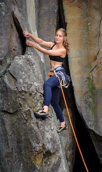 Weiblicher bergsteiger, der mit seil auf einer steilen felsigen wand klettert