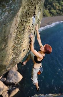 Weiblicher bergsteiger, der ohne seil auf einer felsigen wand klettert