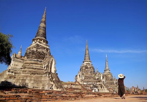 Weiblicher besucher, der entlang der historischen pagodenruinen von wat phra si sanphet ayutthaya thailand geht