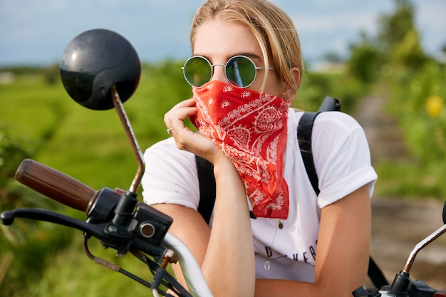 Weiblicher biker, der neben motorrad sitzt