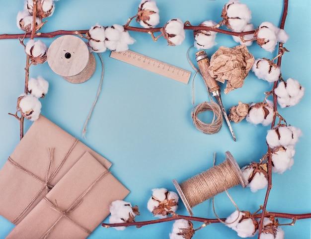 Weiblicher blauer hintergrund mit zweig der baumwollblume. baumwolle, geschenkboxen, juteseilstrang. flache lage, element. .