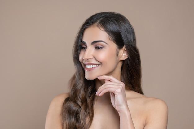 Weiblicher blick. hübsche lächelnde frau, die zur seite schaut und ihren finger zum kinn drinnen berührt