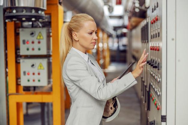 Weiblicher blonder aufseher, der im heizwerk neben armaturenbrett steht, einstellungen anpasst und tablette hält.