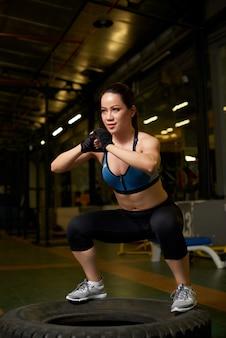 Weiblicher bodybuilder, der auf einem reifen in einer crossfit mitte hockt