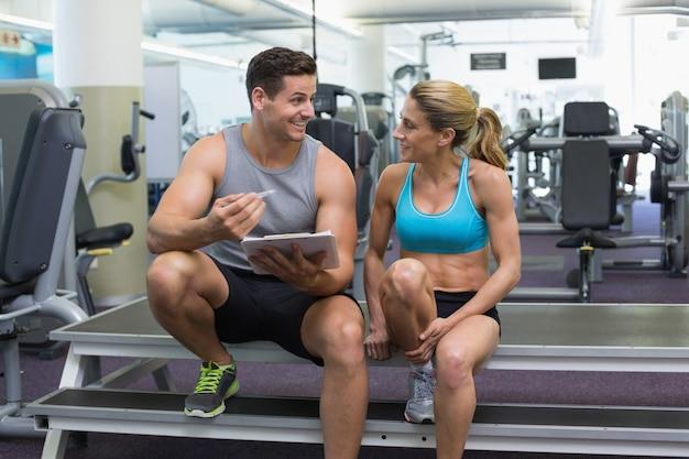 Weiblicher bodybuilder, der mit der persönlichen trainerunterhaltung sitzt