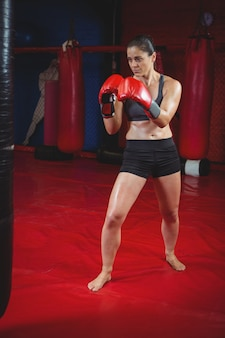 Weiblicher boxer, der einen boxsack schlägt