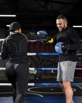 Weiblicher boxer, der im ring mit trainer übt