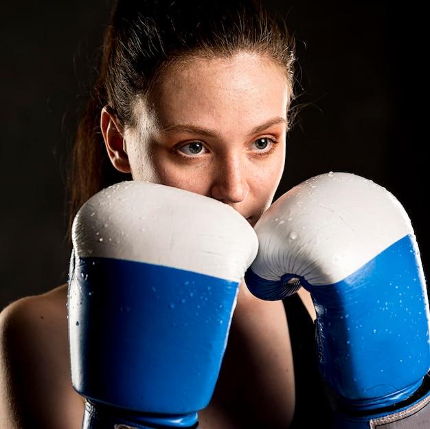 Weiblicher boxer, der mit schutzhandschuhen aufwirft