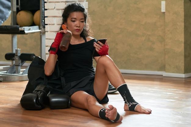 Weiblicher boxer, der mit smartphone nach dem training sich entspannt