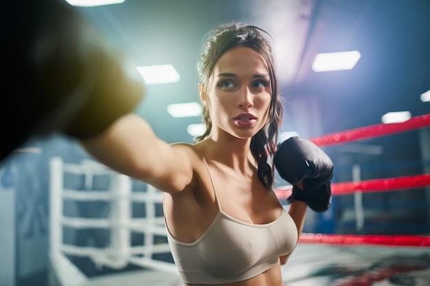 Weiblicher boxer, der treffer in boxhandschuhen zeigt.