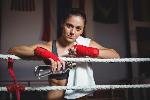 Weiblicher boxer, der wasserflasche im boxring hält