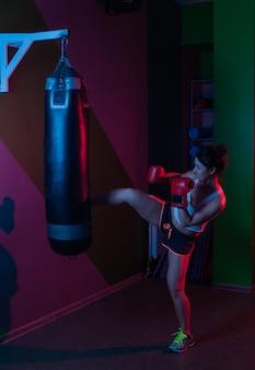 Weiblicher boxer in den boxhandschuhen, die einen boxsack in rotem blauem neonlicht über dunklem hintergrund treten