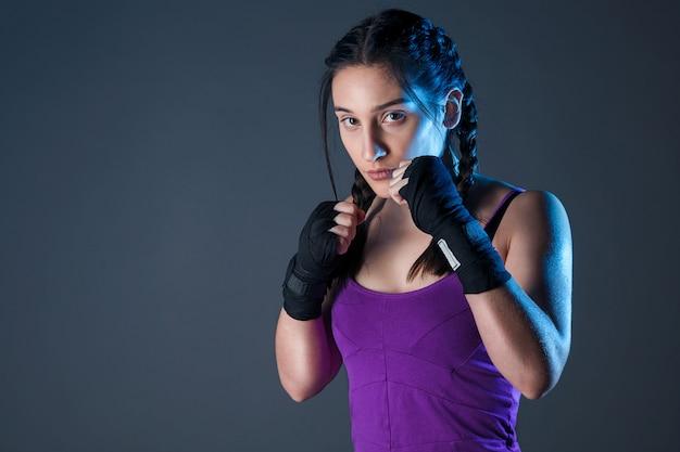 Weiblicher boxer macht einen kampf mit einem schatten, dunkler hintergrund mit platz für text