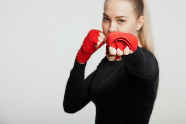Weiblicher boxer macht einen kampf mit einem schatten, weißer hintergrund mit platz für text