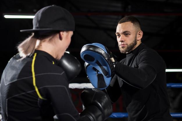 Weiblicher boxer mit schutzhandschuhen übend mit trainer