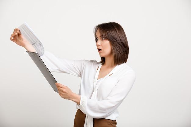 Weiblicher büroangestellter, der bericht liest