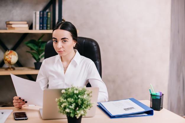 Weiblicher büroangestellter, der dokumente am arbeitsplatz betrachtet