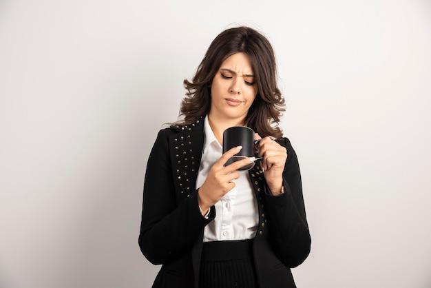 Weiblicher büroangestellter, der eine tasse tee anschaut
