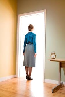 Weiblicher büroangestellter, der in einem eingang untersucht einen raum belichtet mit licht steht