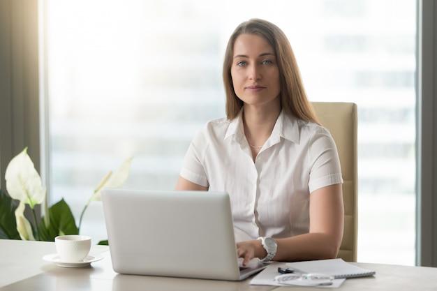 Weiblicher büroangestellter, der tägliche arbeit auf laptop erledigt