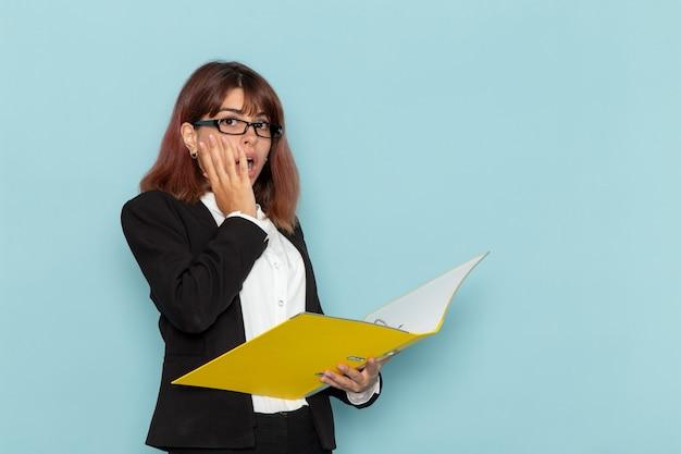 Weiblicher büroangestellter der vorderansicht, der dokument auf der blauen oberfläche hält und liest
