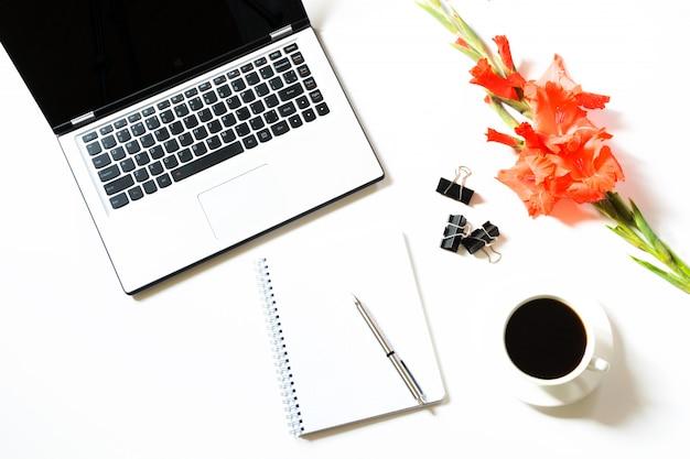 Weiblicher büroarbeitsplatz mit laptop, tasse kaffee, zubehör, gladioleblume auf weiß. unternehmenskonzept.