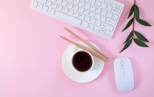 Weiblicher büroarbeitsplatz mit tastatur, computermaus, tasse kaffee und pflanze auf rosa hintergrund. flache lage, draufsicht