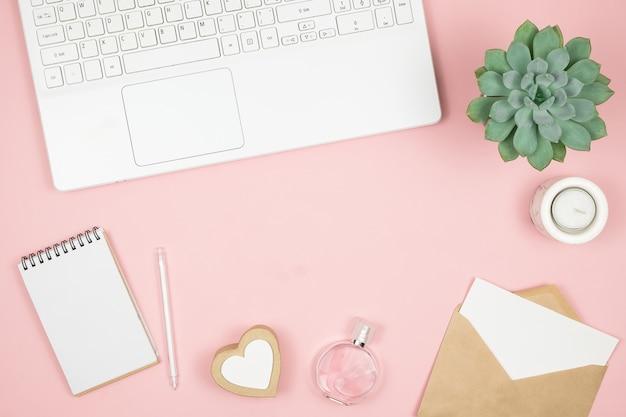 Weiblicher bürodesktop mit bürozubehör auf rosa oberfläche. damenarbeitsbereich mit sukkulenten, kerzen und kosmetika.
