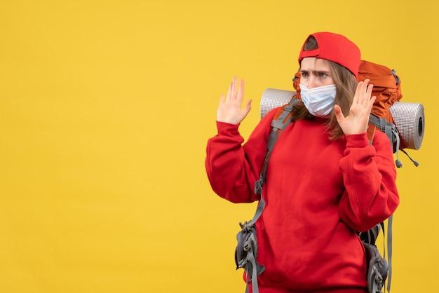 Weiblicher camper der vorderansicht mit rucksack und maske, die stoppschild machen