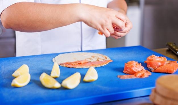 Weiblicher chef bereitet pfannkuchen mit lachsen und kaviar in der küche des restaurants zu