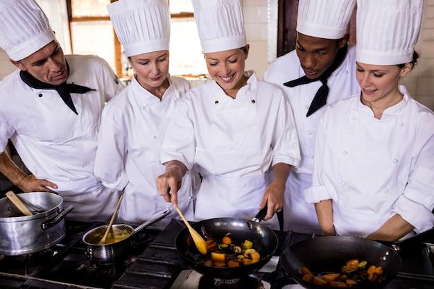 Weiblicher chef, der lebensmittel in der küche zubereitet