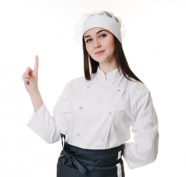 Weiblicher chef, der menü darstellt. netter mädchenchef in der kappe zeigend auf leeren raum.