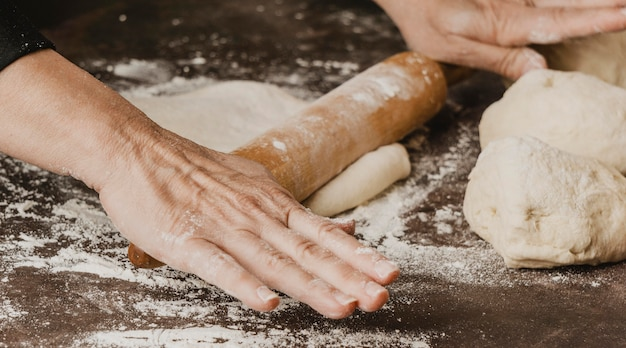Weiblicher chef, der pizzateig auf dem tisch rollt