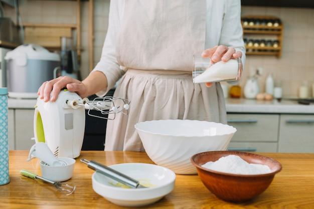 Weiblicher chef, der torte in der küche mit bestandteilen auf tabelle vorbereitet