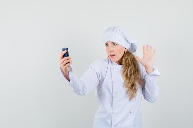 Weiblicher chef in der weißen uniform, die hand beim betrachten des mobiltelefons winkt
