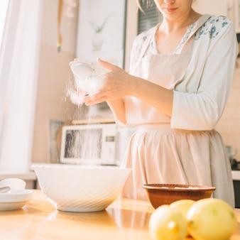 Weiblicher chef in einer küche bereitet teig vom mehl zu, um torte zu machen
