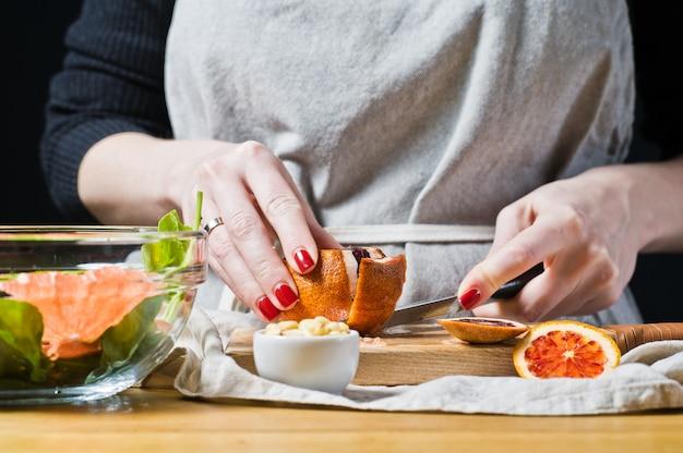 Weiblicher chef schneidet rote orangen für salat mit arugula.