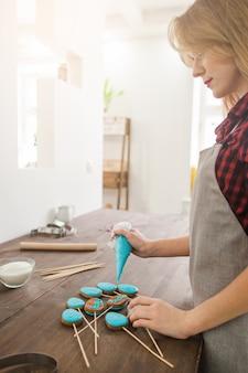 Weiblicher chefkoch, der ostern-blauen kuchen kocht, knallt auf rustikalem holztisch in der küche