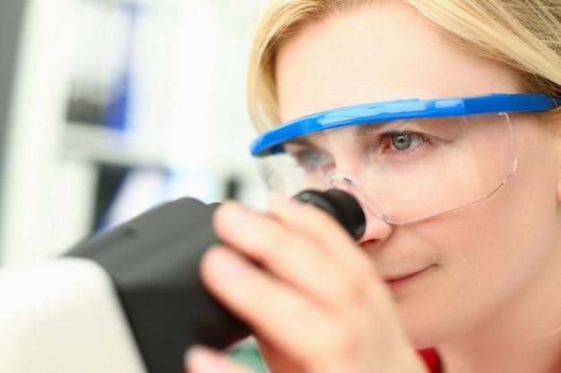 Weiblicher chemiker in den gläsern betrachten mikroskop