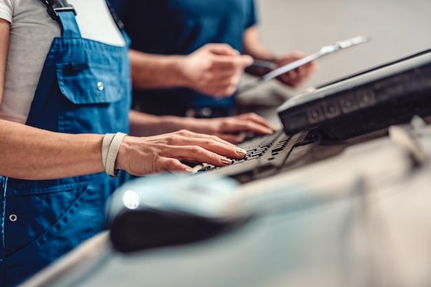 Weiblicher cnc-bediener schreibt herstellungsprogramm auf den computer
