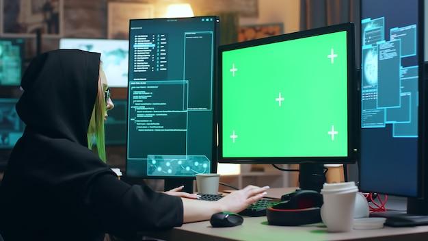 Weiblicher cyber-terrorist, der einen hoodie trägt, der am computer mit grünem bildschirm arbeitet.