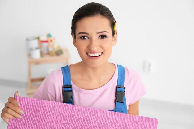 Weiblicher dekorateur, der farbtapeten im innenbereich hält holding