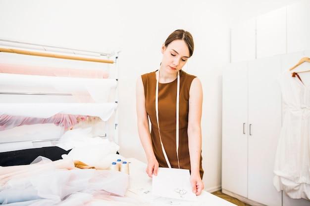 Weiblicher designer, der an modeskizze im studio arbeitet
