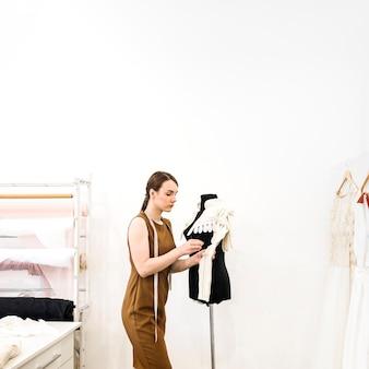 Weiblicher designer, der an stoff im shop arbeitet