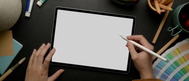 Weiblicher designer, der auf mock-up-tablette mit stift auf dunklem arbeitstisch mit malwerkzeugen zeichnet