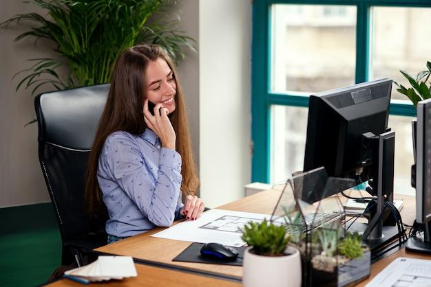 Weiblicher designer, der auf smartphone im modernen büro spricht. schönes mädchen haben ein geschäftsgespräch mit kunden.