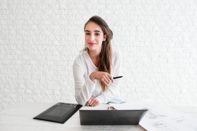 Weiblicher designer, der kamera am arbeitsplatz betrachtet