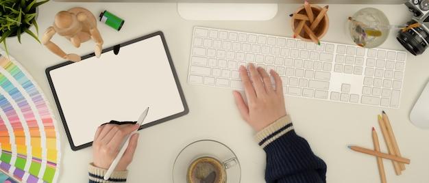 Weiblicher designer, der mit einem tablett, computer auf weißem schreibtisch arbeitet
