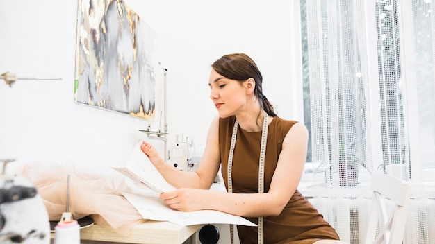 Weiblicher designer, der modeskizze betrachtet