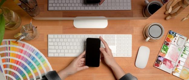 Weiblicher designer, der smartphone beim sitzen am schreibtisch mit computer- und malwerkzeugen verwendet